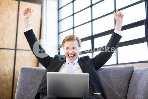 Businessman raising hands with excitement in front of laptop