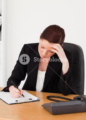 Depressed beautiful redhaired woman in suit writing on a notepad