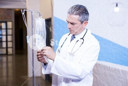 Male doctor checking a saline drip