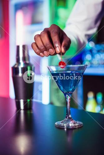 Bartender garnishing cocktail with cherry