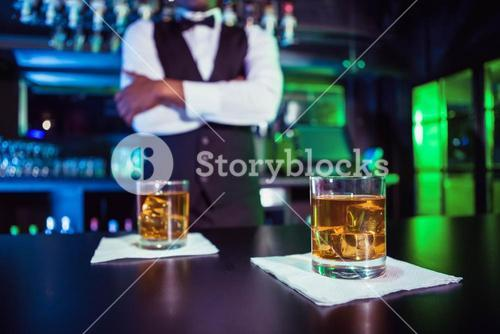 Two glasses of whiskey on bar counter