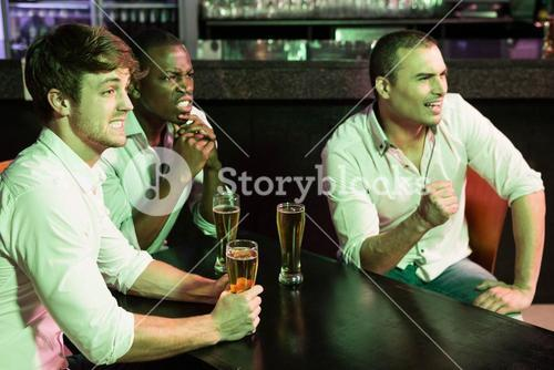 Group of men watching television in bar