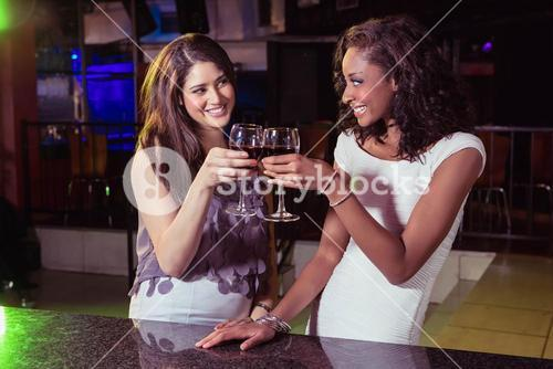 Young women toasting wine glasses at bar counter