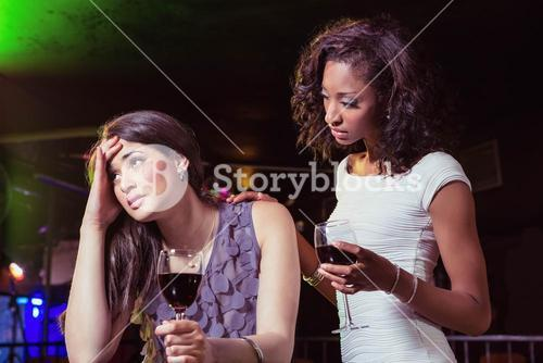 Woman having drinks and comforting her depressed friend