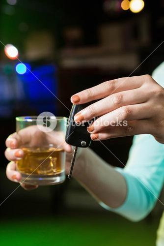 Woman holding a glass of whiskey and car keys