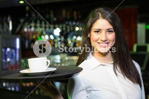 Portrait of pretty waitress serving a cup of coffee
