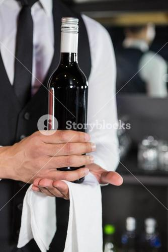 Mid section of bartender holding a wine bottle