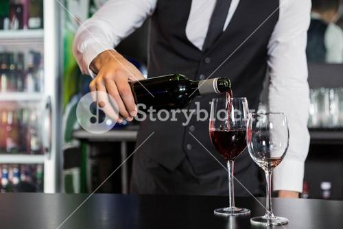 Mid section of bartender pouring red wine in a glass