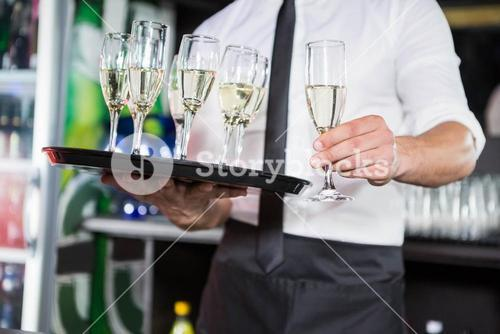 Mid section of bartender serving champagne