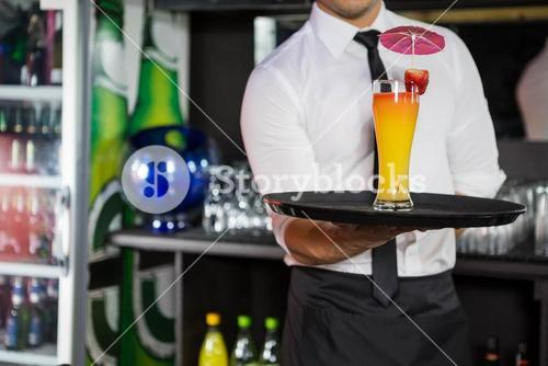 Mid section of bartender serving cocktail