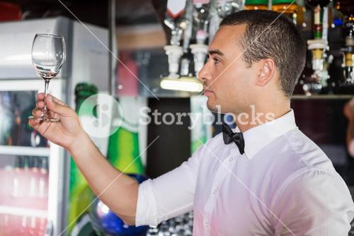 Barkeeper checking a wine glass