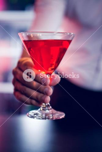 Bartender serving a red martini
