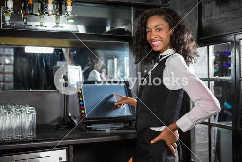 Happy barmaid preparing a bill