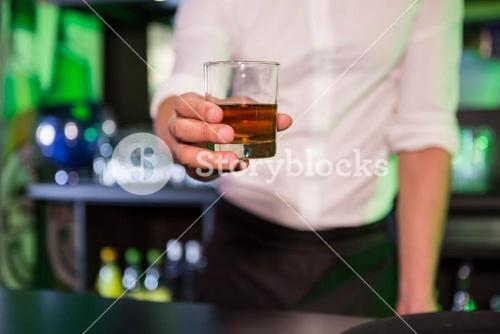 Bartender serving a glass of whiskey
