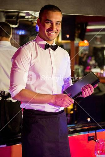 Portrait of waiter standing with a menu card