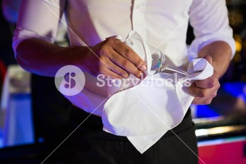 Barkeeper wiping a wine glass