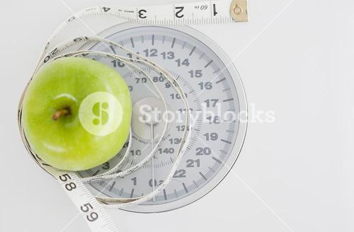 Green apple circled with a tape measure and weighscale