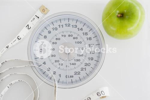 Top view of a green apple along with a tape measure and a weighscale