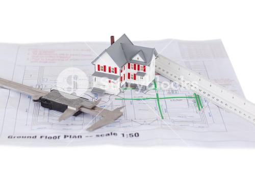 Toy house model and ruler and on a plan against a white background