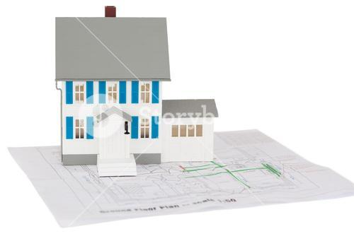 Closeup of a toy house model on a ground floor plan