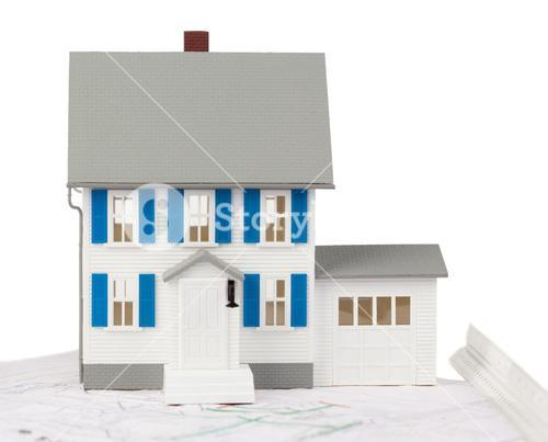 Front view of a toy house model on a ground floor plan