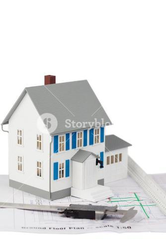 Toy house model and caliper on a ground floor plan