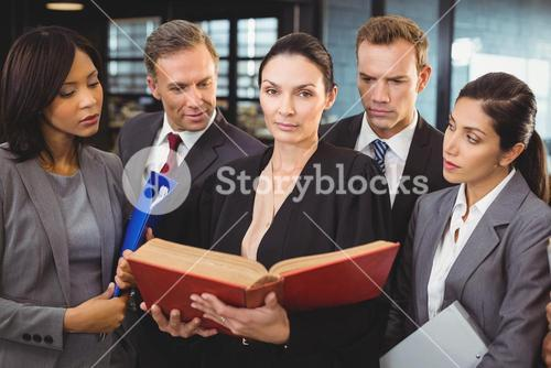 Lawyer reading a law book and interacting with businesspeople