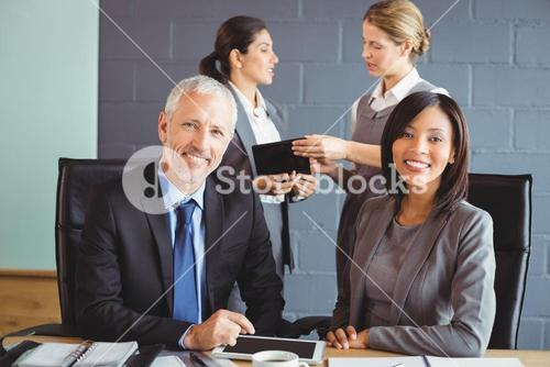 Businessman and businesswoman sitting in conference room