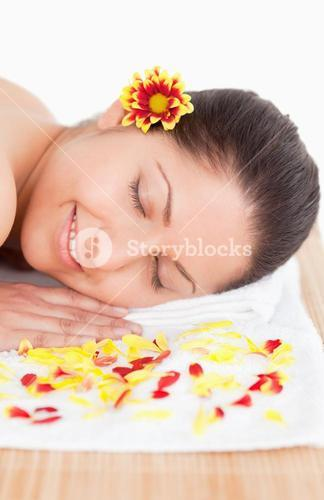 Brunette and flowers petals in a spa