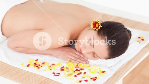 Young woman sleeping with flower petals around her