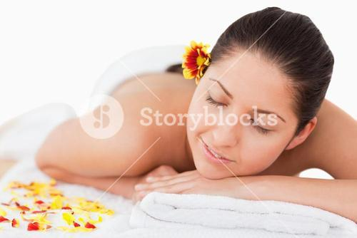 Darkhaired woman closing her eyes and a flower on her ear