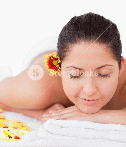 Beautiful woman peacefully smilling surrounded by flower petals