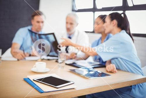 Digital tablet and file on table in conference room