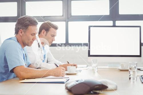 Doctors writing a report in conference room