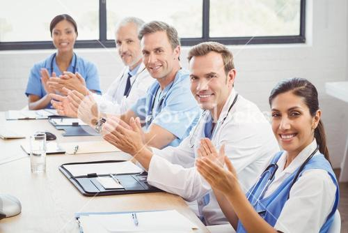 Medical team applauding in conference room