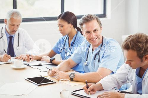 Medical team writing a report in conference room