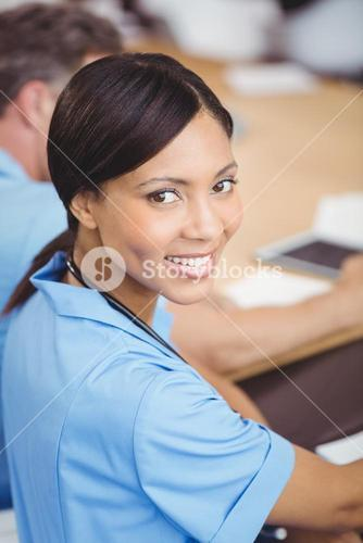 Happy female doctor sitting on conference room