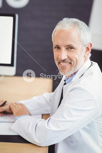 Happy doctor sitting on conference room