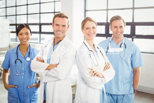 Happy medical team standing with arms crossed