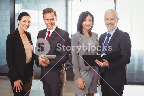 Portrait of happy businesspeople with file and digital tablet