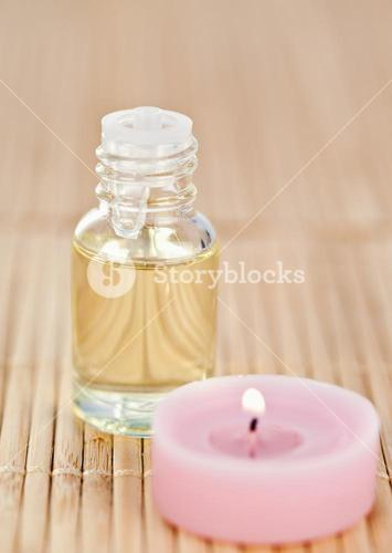 Pink lighted candle and glass phial