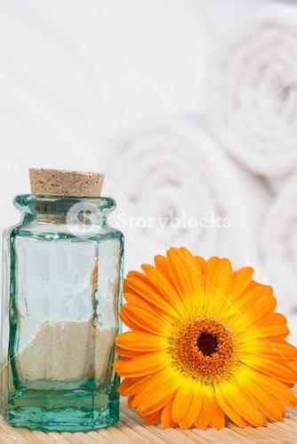 Sunflower with a glass phial and white towels