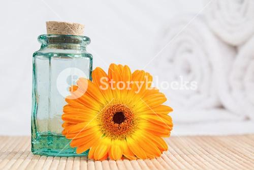 A glass phial and a sunflower with white towels