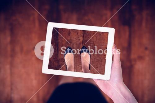Composite image of feminine hand holding tablet