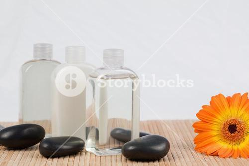Sunflower with black stones and massage oil bottles