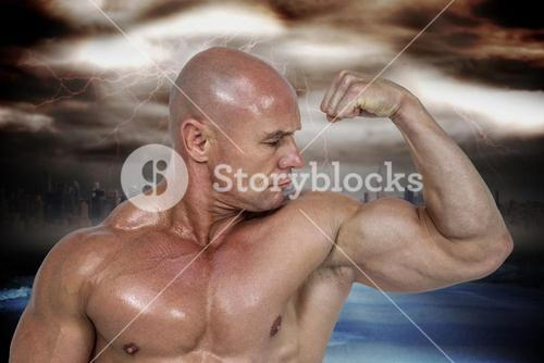 Composite image of muscular man looking at bicep