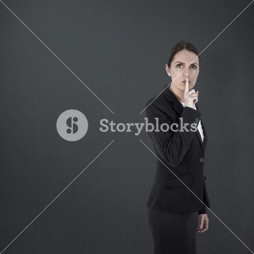 Composite image of businesswoman asking for silence over white background