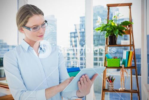 Composite image of businesswoman using tablet pc