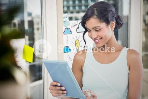 Composite image of smiling businesswoman using digital tablet