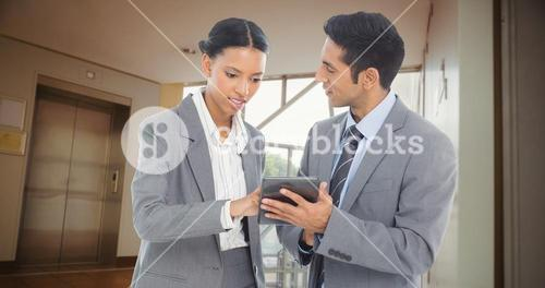 Composite image of business people discussing over digital tablet